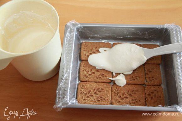 Половину молочно-сливочной смеси распределяем по печенью.