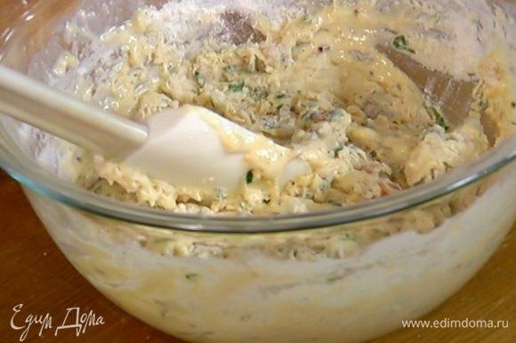 К муке с разрыхлителем добавить молочно-яичную массу и бекон с луком и вымешать тесто.