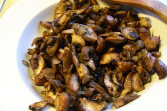 Разогреваем 1 ст. л. оливкового масла и обжариваем лук и грибы без крышки минут 12-15 до испарения всей жидкости. Перекладываем смесь в тарелку.