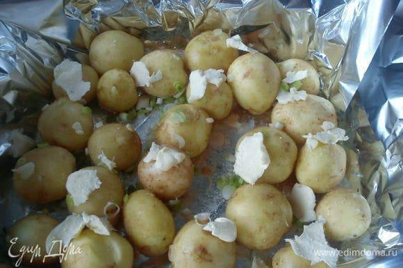 Картофель вымыть щеточкой. Форму для запекания застелить фольгой в несколько слоев. Выложить картофель, посыпать чесноком и солью, сверху разложить кусочками сливочное масло.