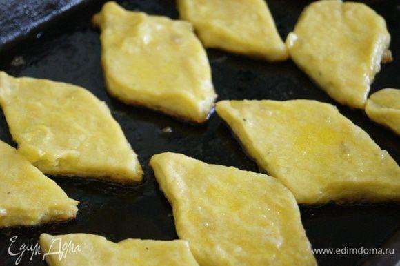 Выложить картофельные ромбики на противень смазанный маслом. Смазать сурки взбитым яйцом и поставить в разогретую до 180 градусов духовку на 10-15 минут