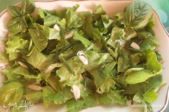 На блюдо порвать листья салата, базилика и порезать лучок.