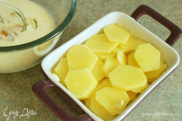 Пока томится мясо, картофель вымыть, очистить и нарезать тонкими ломтиками. Керамическую форму для запекания смазать маслом, уложить в неё картофельные ломтики, посолить и поперчить,