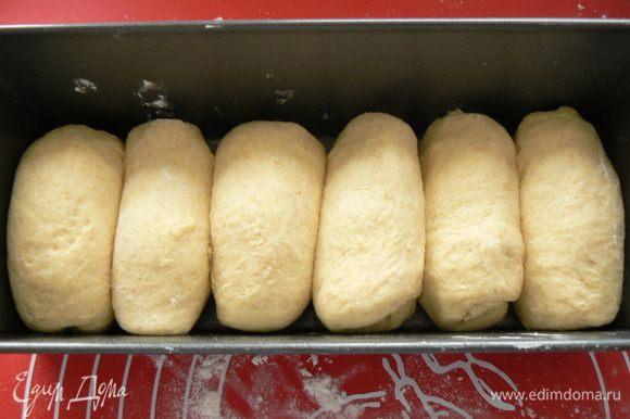 """Подошедшее тесто разделить на 7-8 частей. Сформировать в """"пальчики"""" длиной соответствующей ширине формы для выпечки, выложить их один к другому в форму."""