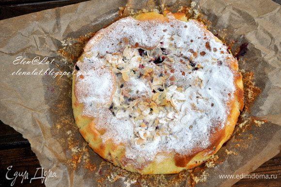 Выложить тесто в форму, застеленную пергаментом, а сверху выложить ягодки. Посыпать все лепестками миндаля. Поставить в заранее разогретую до 180С духовку и выпекать примерно 30-35 минут. Готовность пирога проверить деревянной шпажкой. После того, как он испечется, дать ему немного остыть и присыпать сахарной пудрой и лепестками миндаля.