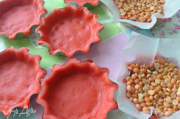 Охлажденное тесто раскатать в пласт толщиной 0,3 см., заполнить им формы для тарталеток. Положить бумагу для выпечки и сверху заполнить горохом или фасолью. Выпекать в разогретой до 180 градусов духовке 15-20 мин.