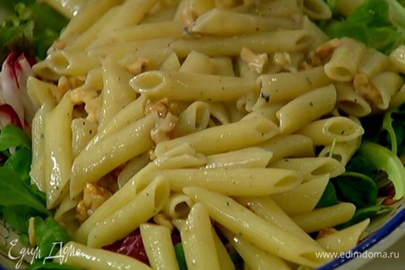 На тарелку поместить листья салата, сбрызнуть оливковым маслом и бальзамическим уксусом, посолить, поперчить и выложить макароны с орехами.