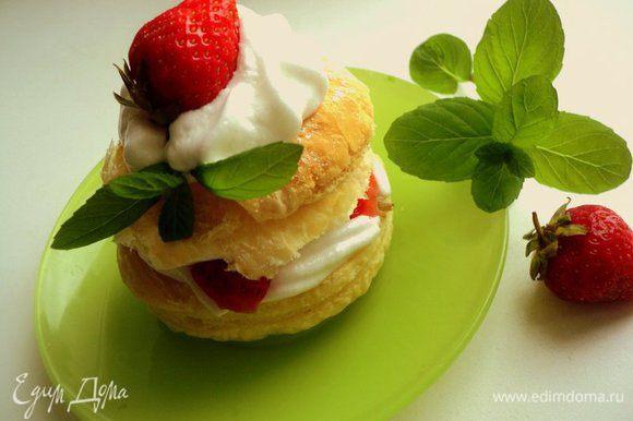 Готовые пирожные посыпать сахарной пудрой, украсить белковым кремом, клубникой и мятой. Получается просто, празднично и вкусно. Приятного аппетита!