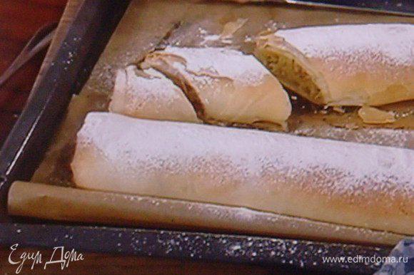 Вынуть штрудель из духовки, присыпать пудрой. Дать ему маленько остыть. Разрезать на порции. Для этого необходим острый нож, т.к. тесто очень ломкое. Красиво смотрится, когда штрудель режут немного наискосок.