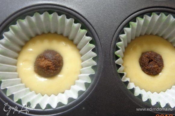 Из коричневого теста скатать шарики и уложить их в центр формочек.