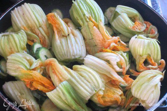 Добавить мелко нарезанную петрушку,посолить,поперчить,хорошо перемешать.Выложить цветки цукини, прогреть несколько минут,снять с огня.
