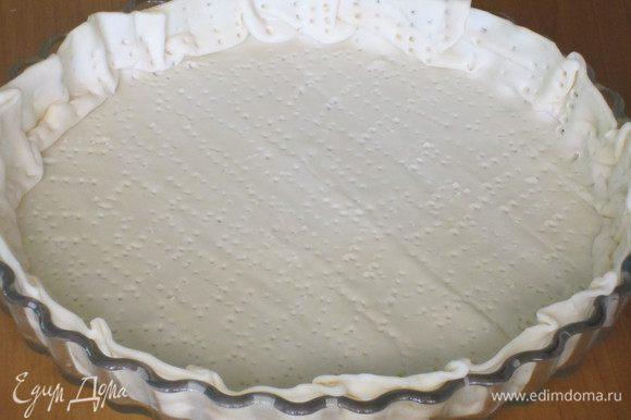 Тесто выложить в форму,наколоть вилкой и посыпать половиной тёртого пармезана.