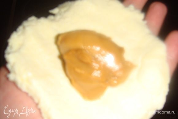 Мокрыми руками делаем лепешку из теста, кладем в середину начинку и формируем сырник