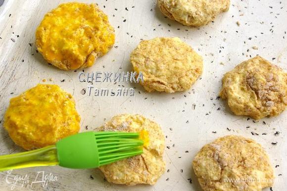 Противень смазываем сливочный маслом. На него укладываем сырники. Слегка взбиваем желток (или яйцо) и смазываем сверху сырники.
