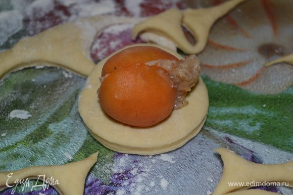 Тесто раскатывем толщиной примерно 0,7-0,8 см. С помощью стакана вырезаем круги. В каждый круг кладем абрикос с начинкой.