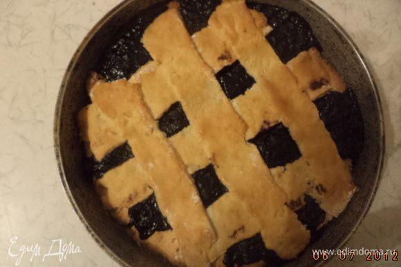 Выложить начинку на тесто. Оставшееся тесто раскатать и разрезать ножом на длинные полосы. Выложить полоски на пирог в виде решётки. Смазать верх пирога молоком. Выпекать 25 минут.