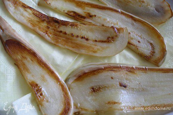 Баклажаны вымыть,нарезать вдоль тонкими ломтиками и обжарить в небольшом количестве масла.Выложить на бумажную салфетку.