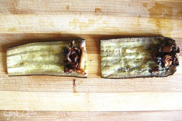 Пластинки баклажанов разрезать на две равные части поперек. На один край каждой пластинки баклажанов выложить немного обжаренных лисичек