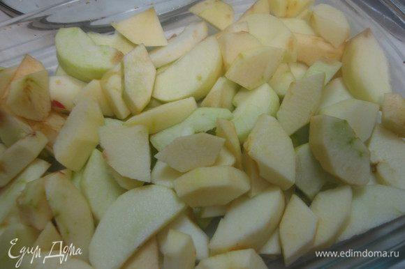 Дно формы выстилаем бумагой. Яблоки чистим, режем дольками, выкладываем на дно формы.