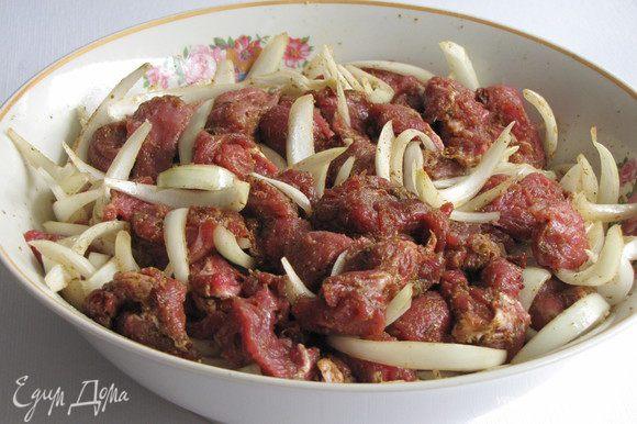 Мясо нарезать небольшими кусочками, добавить аджику, 1 ст. л. растительного масла, лук, нарезанный полукольцами. Все хорошо перемешать и оставить мариноваться на пол часа.