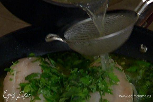 Горячий рыбный бульон и вино влить в сковороду к рыбе, добавить перец чили, накрыть крышкой и готовить 20 минут.