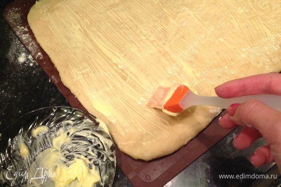 Как только тесто подошло, вымешиваем его до эластичного состояния и раскатываем в квадрат (сторона 23-25 см). Намазываем оставшимся маслом (предварительно немного растопив).