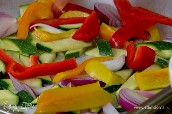 Противень выстелить бумагой для выпечки, выложить цукини, лук и сладкий перец, сбрызнуть оливковым маслом, посолить и поперчить. Отправить противень с овощами под гриль на 5–7 минут.