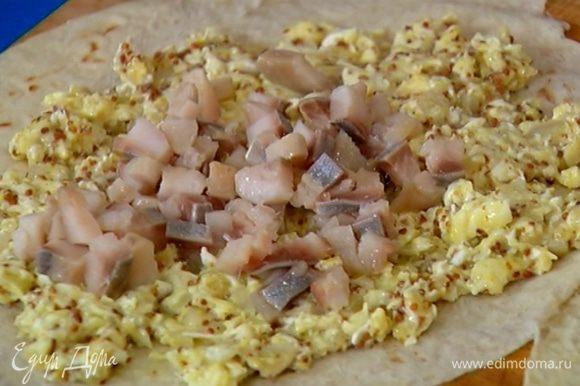 Лаваш разрезать пополам, на одну половину равномерно выложить начинку из яиц, сверху разложить сельдь.