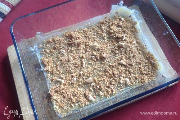 Смазать форму, обильно, сливочным маслом и присыпать половиной раскрошенного печенья.