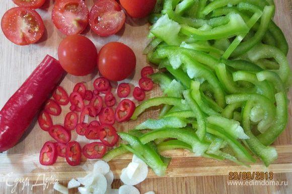 Овощи вымыть. Помидоры разрезать пополам. У перцев удалить сердцевинки. Сладкий перец нарезать соломкой, острый - кольцами. Чеснок тонко нарезать.