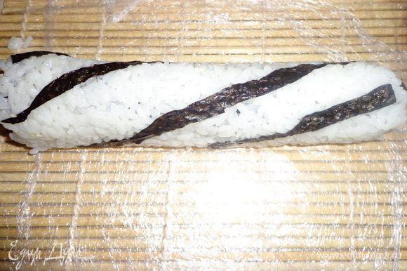 Далее плотно скручиваем, с помощью бамбукового коврика. Роллы с семгой я выкладывала на рис, т.е. не переворачивая нории рисом вниз. Острым нож и нарезаем на 6-8 кусочков. Нож каждый раз необходимо промывать под холодной водой, иначе рис будет прилипать и мешать резать.