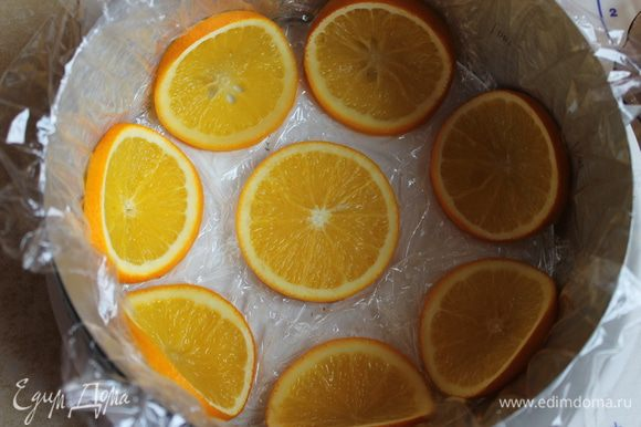 Когда апельсины будут готовы, даeм им остыть. Возьмем форму 20см, если нет такой , то можно взять кольцо (как сделала я) и выстилить его пленкой. И берем наши кружочки выкладываем вот таким образом,сгибаем их посередине, они будут гнуться очень хорошо. Примерно у мeня ушло 8 штук.Если же вы возьмете форму, то ее можно обмазать и обсыпать сахаром.