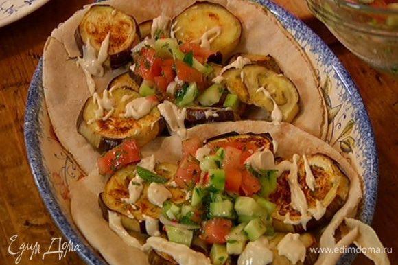 Теплые лепешки положить на блюдо, на них поместить баклажаны, сбрызнуть соусом, сверху выложить овощной салат.