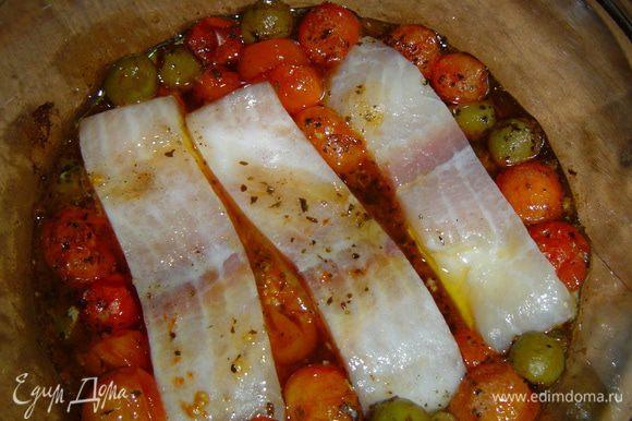Достаем помидорно-оливковую смесь из духовки, томаты раздвигаем, а в середину выкладываем кусочки рыбного филе,