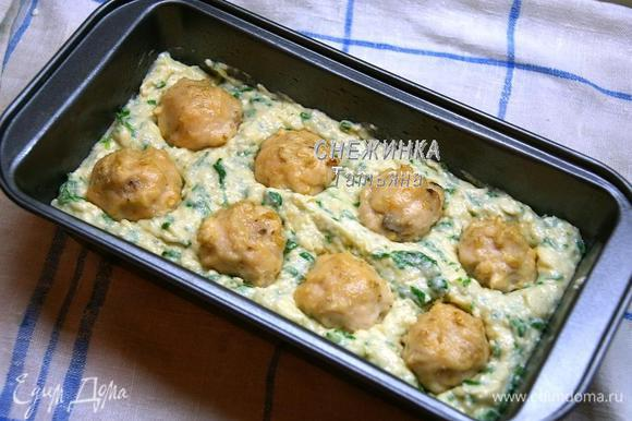 Прямоугольную форму для кекса смазываем маслом. Выкладываем половину теста. Кладём куриные шарики, немного вдавливая в тесто.