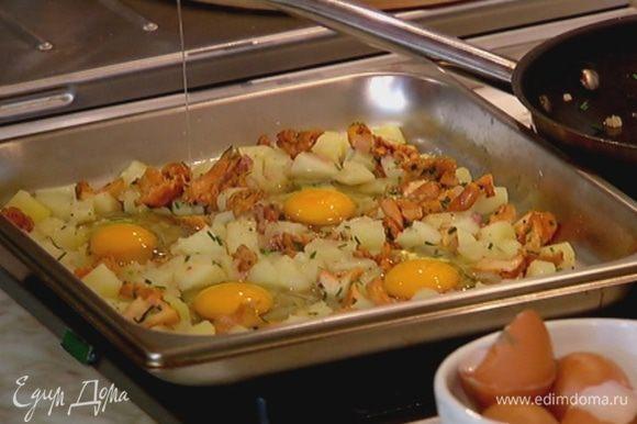 Вынуть противень с картофелем из духовки, выложить сверху обжаренные лисички с луком, все перемешать, лопаткой сделать четыре углубления и разбить в них яйца.