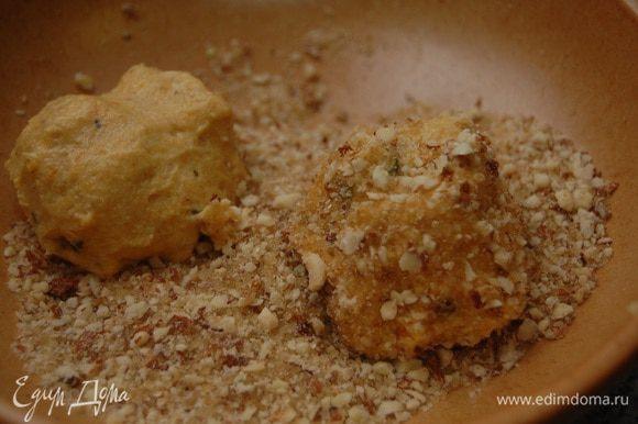 Мокрыми руками сформировать шарики (вес каждого около 60 г), обвалять в ореховой крошке, выложить на пекарскую бумагу и слегка придавить рукой, придав форму лепешки.