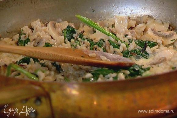 Выложить к грибам отваренный рис, перемешать и снять сковороду с огня.