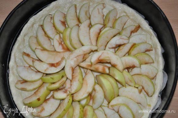 На тесто равномерно распределить ломтики яблок, посыпать сахаром,