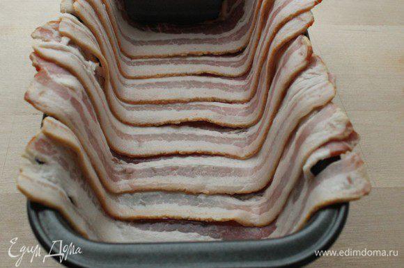 В прямоугольную форму внахлест выложить пластинки бекона, чтобы края свисали.