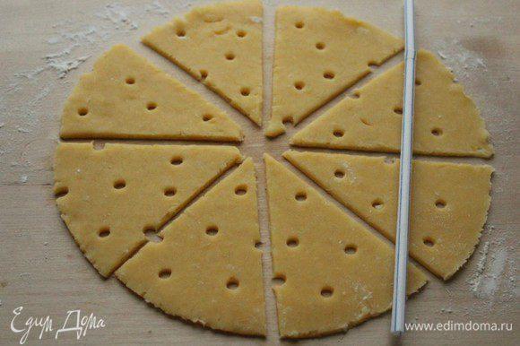 Тесто разделить на две части. Раскатать круглый корж, разрезать на треугольники и при помощи коктейльной трубочки сделать отверстия. (так называемые сырные дырки)))