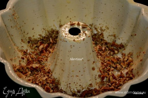 Смазать хорошо форму с дыркой сливочным маслом, обсыпать мукой. Порубить пекан в крошку . Выложить поверх формы.