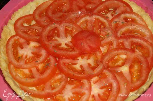 Когда основа для пирога стала золотистой, достаем и даем ей остыть. Нарезанные тонкими кольцами помидоры выкладываем внахлест на готовое тесто.