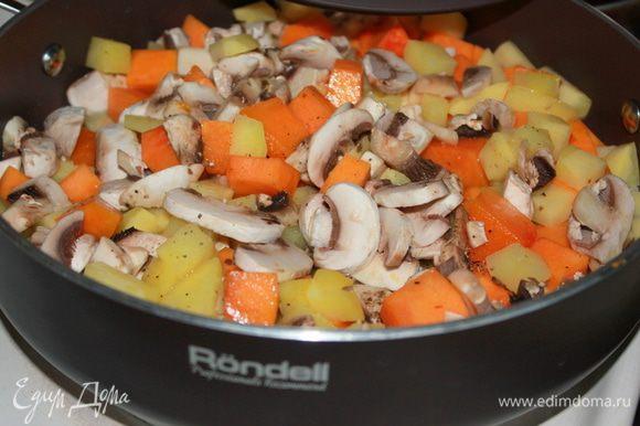 Грибы нарежьте небольшими кусочками. Чеснок очистите, раздавите плоской стороной ножа. В сотейнике разогрейте растительное масло. Добавьте картофель, тыкву, грибы и чеснок. Накройте крышкой и тушите на среднем огне около 10 минут, периодически помешивая.
