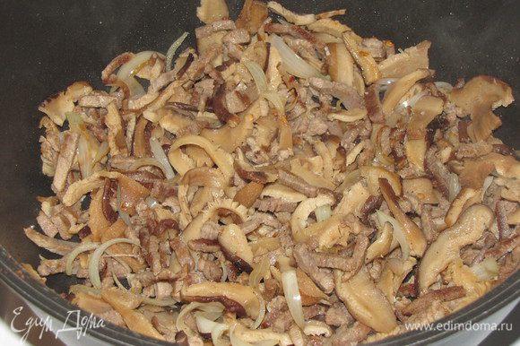 Отваренные грибы отжать и добавить к мясу. Если нужно, добавить еще кунжутное масло. Все перемешать и жарить минуты 3.
