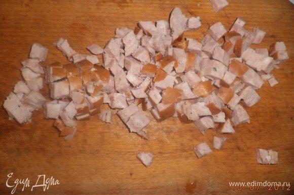 Колбасу нарезать мелкими кубиками. Чеснок очистить и пропустить через чеснокодавку.