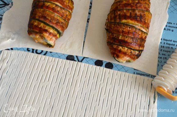 Духовку разогреть до 200 С. Слоеное тесто раскатать в тонкий пласт прямоугольной формы. Отрезать 1/3 полоски теста, разрезать пополам, у нас получится 2 прямоугольника. Положить на них уже остывшие грудки. Оставшееся тесто надрезать, используя специальный нож, или сделать надрезы обыкновенным ножом...