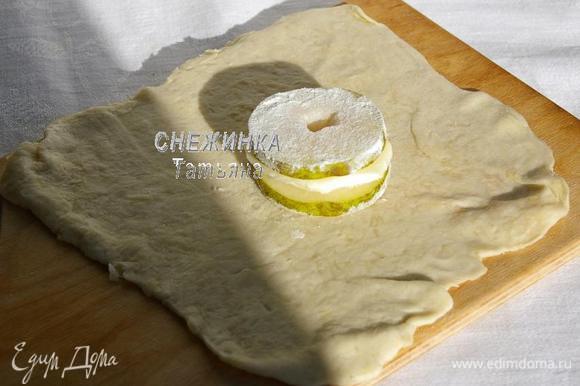 Раскатанное тесто с сыром делим на 2 равные части. Каждую из них ещё раз раскатываем, чтобы получился тонкий квадрат, сыр должен быть виден своеобразными «прожилками». Кружок груши обмакиваем в муку с одной стороны и кладём её на тесто. На грушу кладём кружок моцареллы, на моцареллу – второй кружок груши, сверху припыленный в муке.