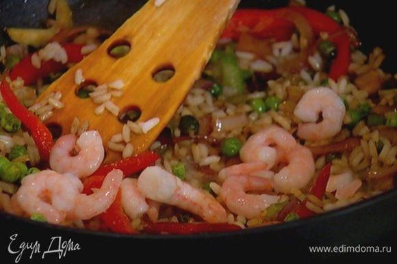 Слить из креветок солевой раствор и добавить их к рису с овощами. Все прогреть, перемешивая.