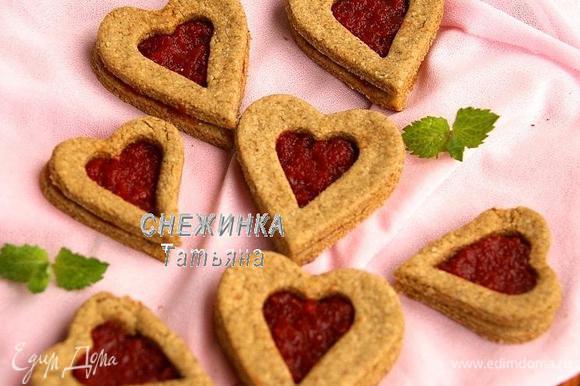Готовые печенья снимаем с противня и даём полностью остыть. Целые сердечки смазываем небольшим количеством джема и сверху накрываем сердечками с вырезанным центром.